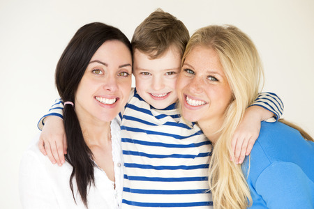 female sex: Same sex female couple posing with their son in front of a plain background Stock Photo