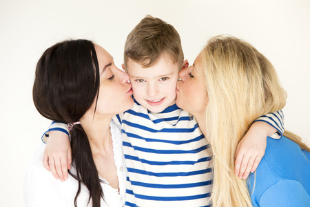 same sex: Same sex couple kissing eitherside of their sons face for the camera. Stock Photo