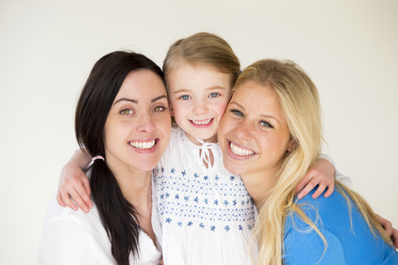 same sex: Same sex female couple posing with their daughter in front of a plain background