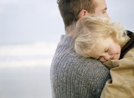 child protection: Little girl being carried on the beach by her father. She has her head on his shoulder.