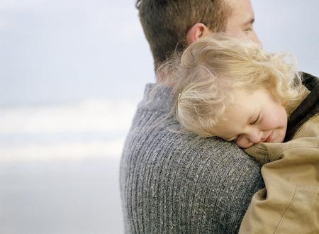 Meisje op het strand wordt gedragen door haar vader. Ze heeft haar hoofd op zijn schouder. Stockfoto - 42709193