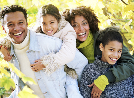 fall time: Family of four posing together in the woods. They father is carrying the little girl whilst the mother has her arm around the son. Stock Photo