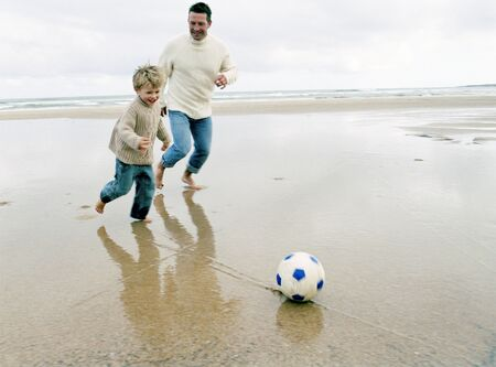 Father playing football on the beach with his son. photo
