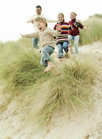 Familie van vier die samen spelen en rennen een met gras begroeide bank op het strand.