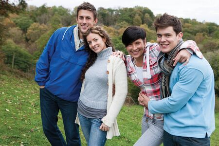 rou: Two couples who are also friends, stand together and smile for the camera whilst outdoors. One girl has her head on her partners shoulder, who has his arm wrapped round her waist. The other woman has her hand on her friends shoulder with her other arm rou Stock Photo