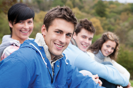 four person only: Close up of four friends sitting on a grassy hill and smiling for the camera. The man at the front is the only person in focus.The four people can be seen from the shoulders up, with trees out of focus in the background