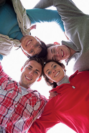 leaning forward: Four friends have their arms round each other and are leaning forward with their heads together. They are looking down at the camera and smiling.