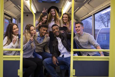 バスの後ろに selfie を取る若い大人のグループ。
