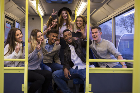 Group of young adults taking a selfie at the back of a bus.