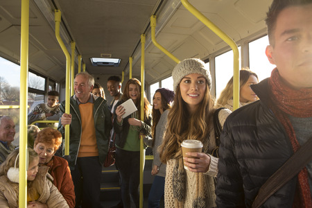 Different people can be seen travelling on the bus. Some are talking to other people, others are using technology or looking out the window.