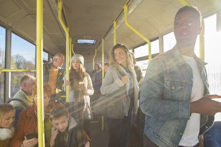 old bus: Different people can be seen travelling on the bus. Some are talking to other people, others are using technology or looking out the window.