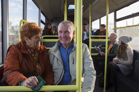 Senior couple travelling on the bus. There are other people sat on the bus who are in the background. Stock Photo