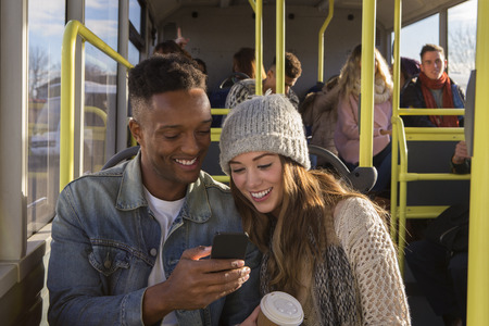 Young couple on a bus. They are both looking at something on a smartphone and smiling. There are people in the background who are also on the bus.