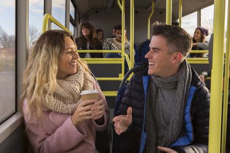 Pareja joven  amigos que charlan en un autobús junto. Hay otras personas en el autobús en el fondo.