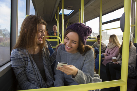 Two young women on a bus. They are both looking at something on a smartphone and smiling. There are people on the bus in the background.
