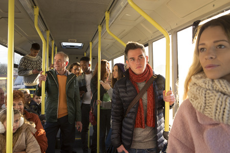 mixed race people: Different people can be seen standing and sitting in a bus. Some are talking, others are looking out the window.