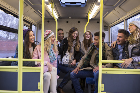 scarves: Group of young adults sitting together at the back of the bus. They are laughing and talking.