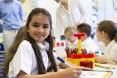 Portrait of a cute young schoolgirl smiling at the camera while sitting at her desk.