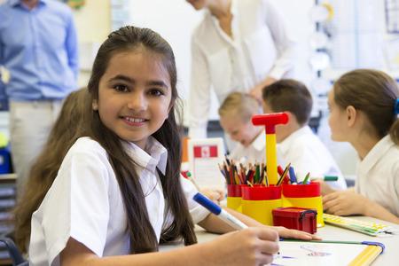 maestra enseñando: Retrato de una joven colegiala linda sonriendo a la cámara mientras está sentado en su escritorio.