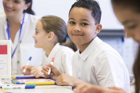 78: School boy smiles at the camera as he sits at his desk while working. Stock Photo