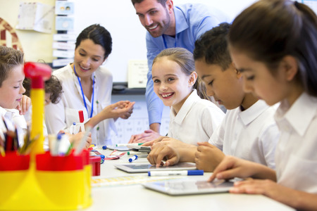 Un groupe d'enfants de l'école peut être vu travailler sur des tablettes numériques, deux enseignants peuvent être vus derrière les aider et de la supervision Banque d'images