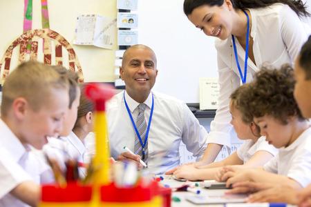 ni�os estudiando: Un profesor de sexo masculino se sienta supervisar a un grupo de ni�os que trabajan en las pizarras y tabletas digitales.