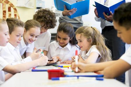 Un grupo de niños de la escuela puede ser visto trabajando en tabletas digitales y pizarras, todos están trabajando felizmente. Dos maestros irreconocibles se pueden ver en el fondo.