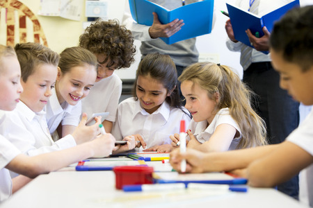 niños sentados: Un grupo de niños de la escuela puede ser visto trabajando en tabletas digitales y pizarras, todos están trabajando felizmente. Dos maestros irreconocibles se pueden ver en el fondo.
