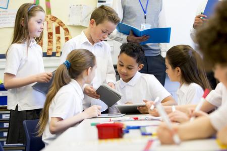Een groep schoolkinderen te zien werken aan digitale tablets en whiteboards, zijn ze allemaal graag werken. Twee onherkenbaar leraren kan worden gezien in de achtergrond.