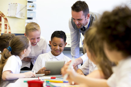 uniforms: A male teacher sits supervising a group of children who are working on whiteboards and digital tablets.