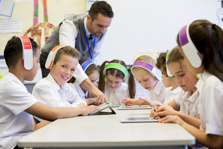 classroom: Group of children wearing colourful wireless headsets while working on digital tablets, the teacher can be seen supervising the students in the classroom Stock Photo