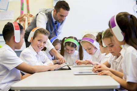aula: Grupo de niños que usan audífonos inalámbricos de colores mientras se trabaja en tabletas digitales, el profesor puede verse la supervisión de los estudiantes en el aula