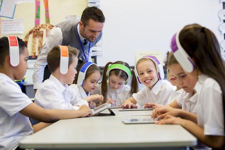 uniforme escolar: Grupo de niños que usan audífonos inalámbricos de colores mientras se trabaja en tabletas digitales, el profesor puede verse la supervisión de los estudiantes en el aula