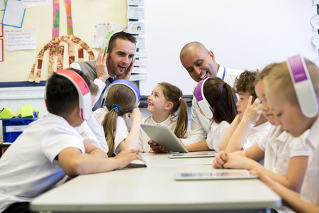 Group of children wearing colourful wireless headsets while working on digital tablets, two teachers can be seen supervising the students in the classroom Reklamní fotografie - 43346191