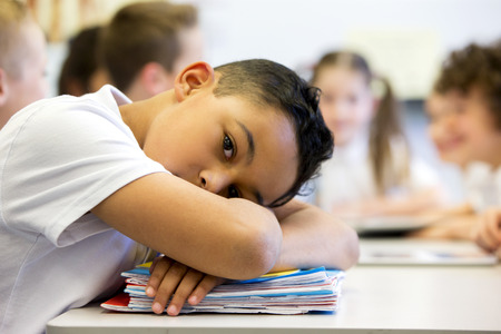elementary student: A close up shot of a little boy at school who looks distant and upset.