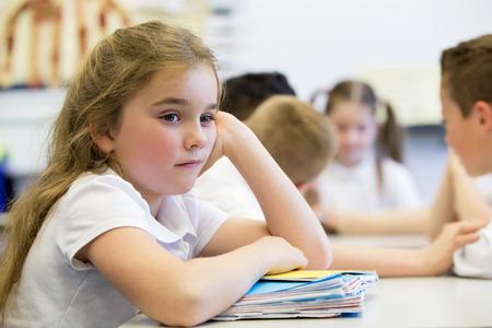 školačka: Zblízka záběr holčička ve škole, která vypadá vzdálená a rozrušený.