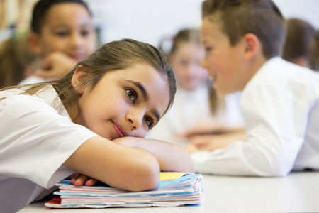 78: A close up shot of a little girl at school who looks distant and upset. Stock Photo