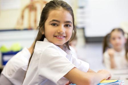 ni�as peque�as: Ni�a de la escuela sonr�e a la c�mara mientras se sienta en su escritorio durante el trabajo.