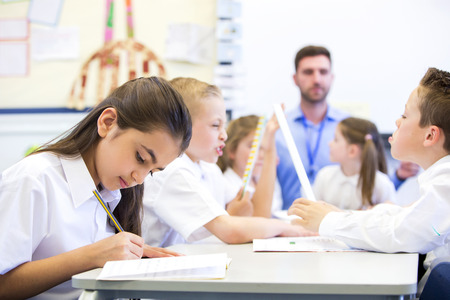 Schoolgirl sitting at a desk with other classmates while working. Her head is down while she concentrates. The teacher can be seen in the background.