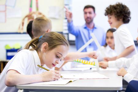 Schoolmeisje zittend aan een bureau met andere klasgenoten tijdens het werk. Haar hoofd naar beneden, terwijl ze zich concentreert. De leraar kan worden gezien in de achtergrond.