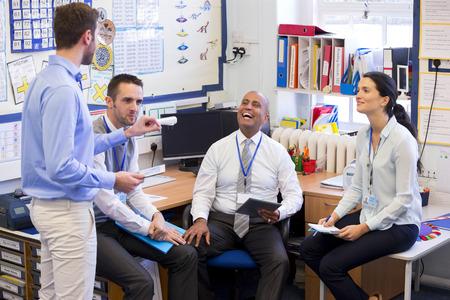 profesores: Los maestros de escuela se reúnen en una pequeña oficina de la escuela para charlar. Se ven felices. Una mujer y tres hombres grupo juntos.