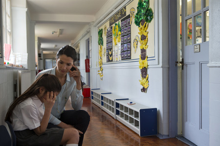 A female teacher sits consoling a young student in the corridor, the little girl looks very upset and holds her head in her hands.