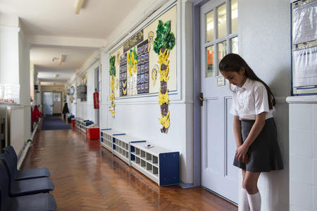 Naughty school girl stands in the corridor after being sent out of class. Standard-Bild