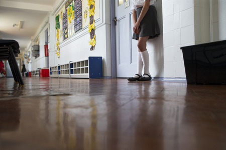 Naughty school girl stands in the corridor after being sent out of class. Stockfoto