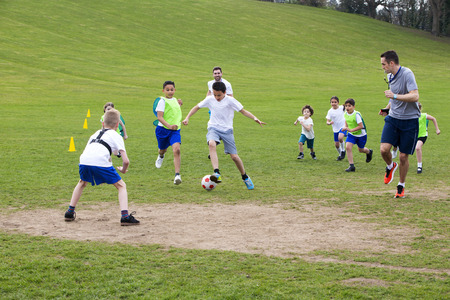 practice: Adults on grassed area with school children supervising a soccer game, Everyone can be seen running and chasing the ball. Stock Photo