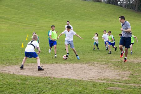 Dospělí na zatravněné ploše s školní děti dohlížet na fotbal, Každý může být viděn spuštěn a honí míč.