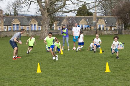 spielende kinder: Erwachsene auf Grünfläche mit Schulkindern Überwachung eines Fußballtraining, kann jeder sehen Kegel rund laufen. Schulhaus kann im Hintergrund gesehen werden.