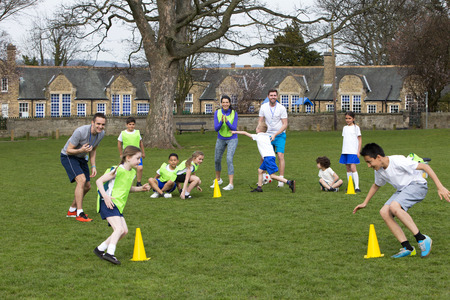 SCUOLA: Adulti in zona erba con i bambini delle scuole supervisione di una sessione di allenamento di calcio, tutti possono essere visti in giro coni. Edificio scolastico pu� essere visto in background.