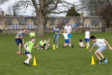 Volwassenen op gazon met schoolkinderen het toezicht op een voetbal training, kan iedereen zien lopen rond kegels. Schoolgebouw kan worden gezien in de achtergrond. Stockfoto
