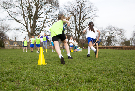 training group: School children wearing sports uniform running around cones during a physical education session. Stock Photo